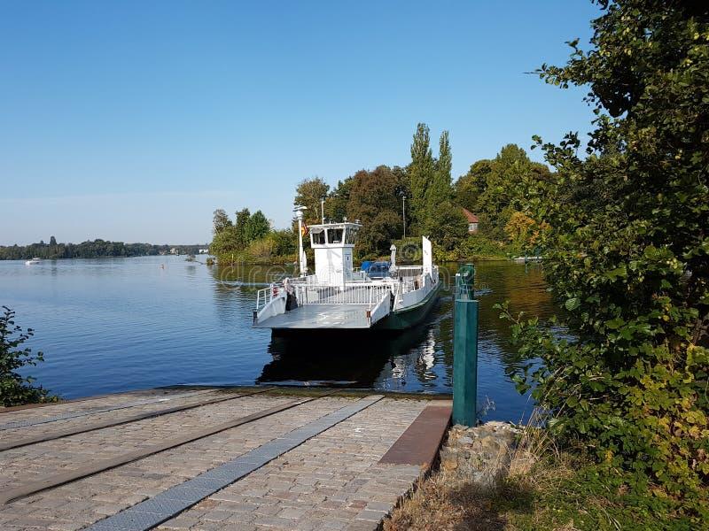 Ferry au pilier avec une voiture à l'arrière photos stock