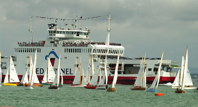 Ferry Boat and dinghies at cowes Week 2010. Isle of Wight Ferry amidst a dinghy race during Cowes Week 2010 stock photo