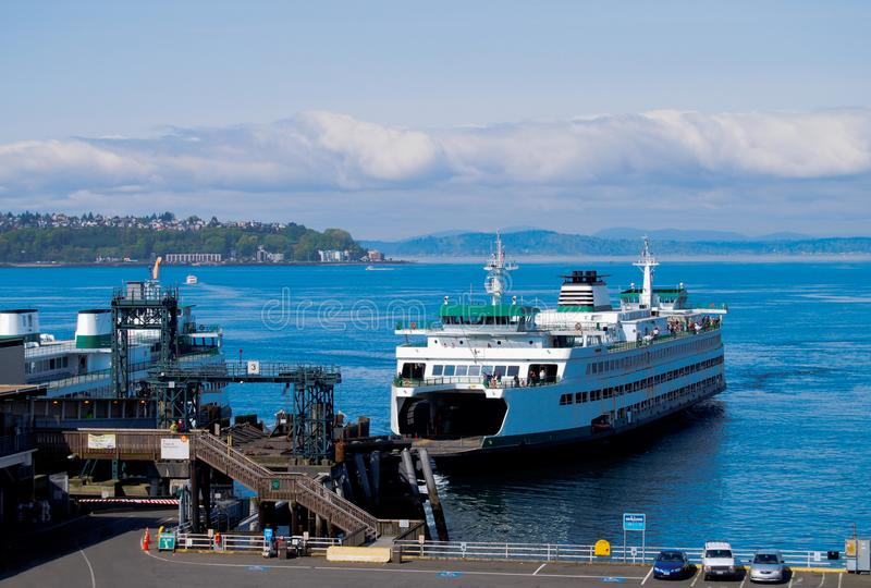 Ferry Boat At Dock Load Cars and Pedestrians. Ferry boat arriving at Seattle port to take on cars and walk on passengers for commute across Puget Sound. The stock images