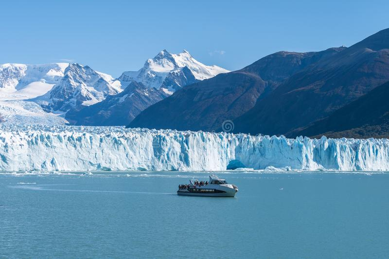 Ferry boat in front of Perito Moreno glacier, blue ice burg glacier from peak of the mountain through the blue lake in Los stock photography
