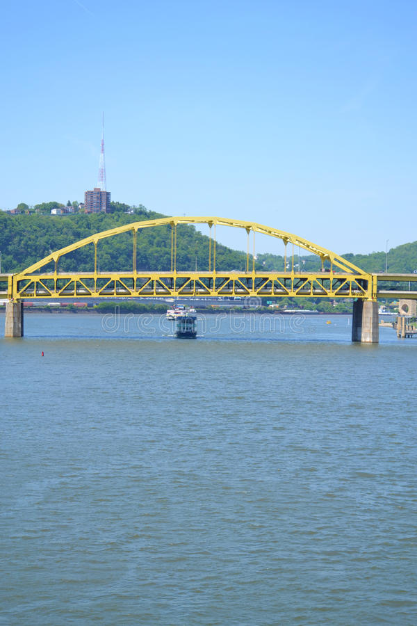 Ferry Boat on the Ohio River in Pittsburgh, PA. Ferry boat travels under yellow roadway bridge on the Ohio River in Pittsburgh, Pennsylvania stock photography