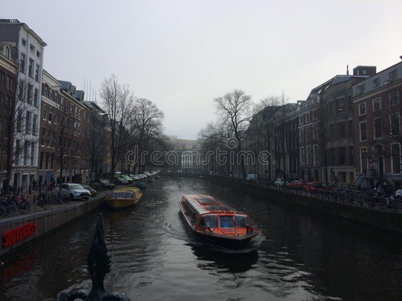 Ferry de canal croisant par le canal d'Amsterdam photo stock