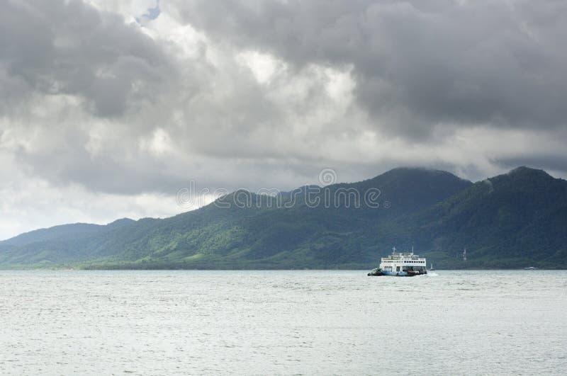 Ferry de cargaison en mer tropicale sous les nuages lourds de tempête de mousson et île tropicale de Koh Chang sur l'horizon en T photos stock
