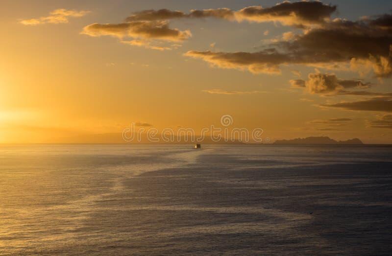 Ferry de matin naviguant loin aux îles éloignées dans la lueur de matin du lever de soleil photographie stock