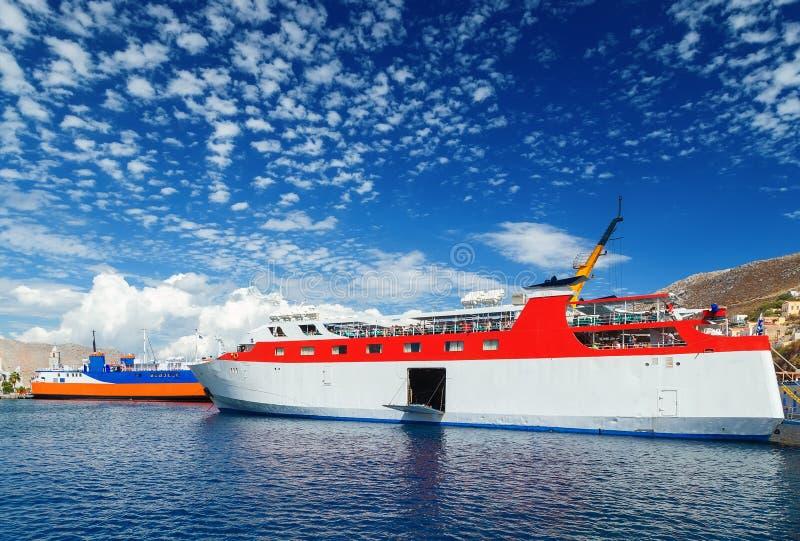 Ferry de mer de passager de deux Grecs du trafic maritime régulier de Dodekanisos dans la baie de l'île de Simi au fond des colli photos stock