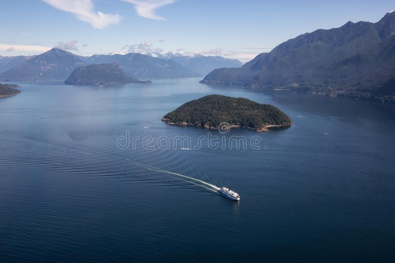 Ferry in Howe Sound Aerial View. Howe Sound, Vancouver, BC, Canada - July 21, 2018: Aerial view of BC Ferry traveling in the ocean during a vibrant sunny summer royalty free stock image