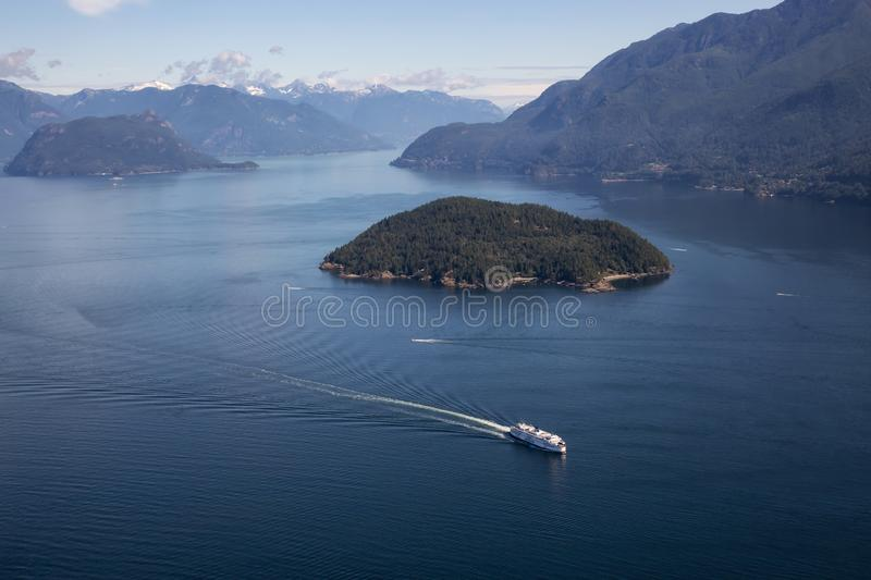 Ferry in Howe Sound Aerial View. Howe Sound, Vancouver, BC, Canada - July 21, 2018: Aerial view of BC Ferry traveling in the ocean during a vibrant sunny summer stock photography