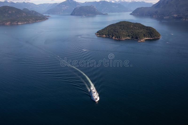 Ferry in Howe Sound Aerial View. Howe Sound, Vancouver, BC, Canada - July 21, 2018: Aerial view of BC Ferry traveling in the ocean during a vibrant sunny summer royalty free stock images
