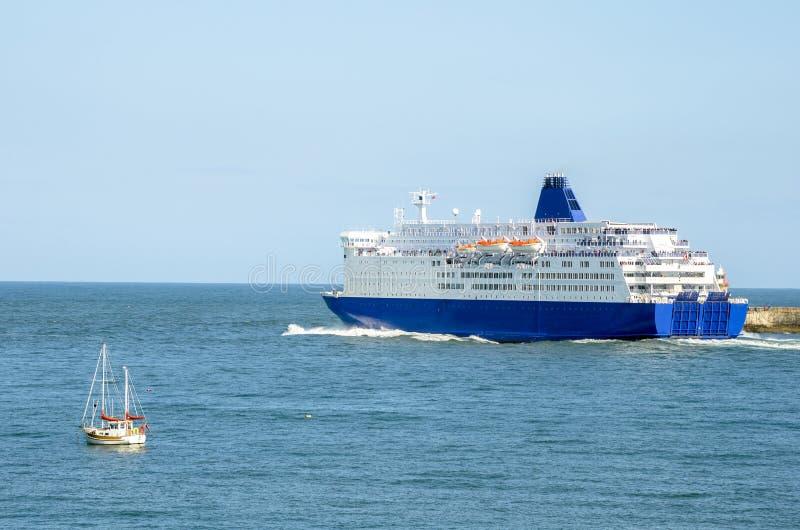 Ferry laissant le port sous le ciel bleu photos stock