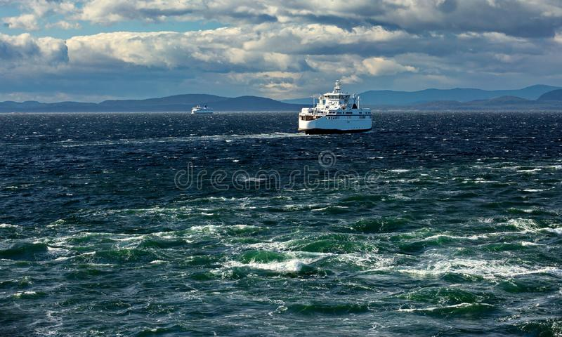 BC Ferry in Strait of Georgia. The ferry makes a regular flight from Vancouver to Nanaimo, windy day, stormy sky, stormy sea, blue water with a green tint royalty free stock images