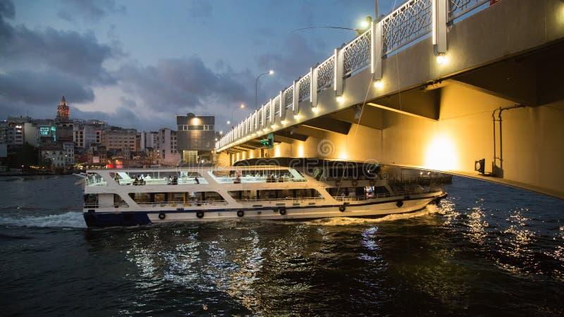 Ferry a passagem sob a ponte de Galata na noite Chifre dourado Turquia, Istambul imagem de stock