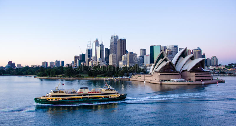Ferry passes in front of Sydney Opera House with the city in the background royalty free stock photo
