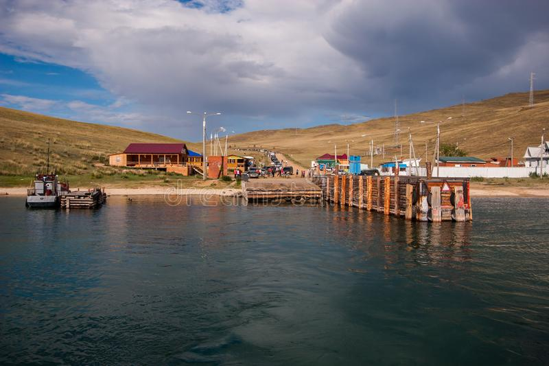 Ferry pier Olkhon island with waiting cars and people. On the shore are wooden houses, lampposts. Over the hills clouds royalty free stock photo