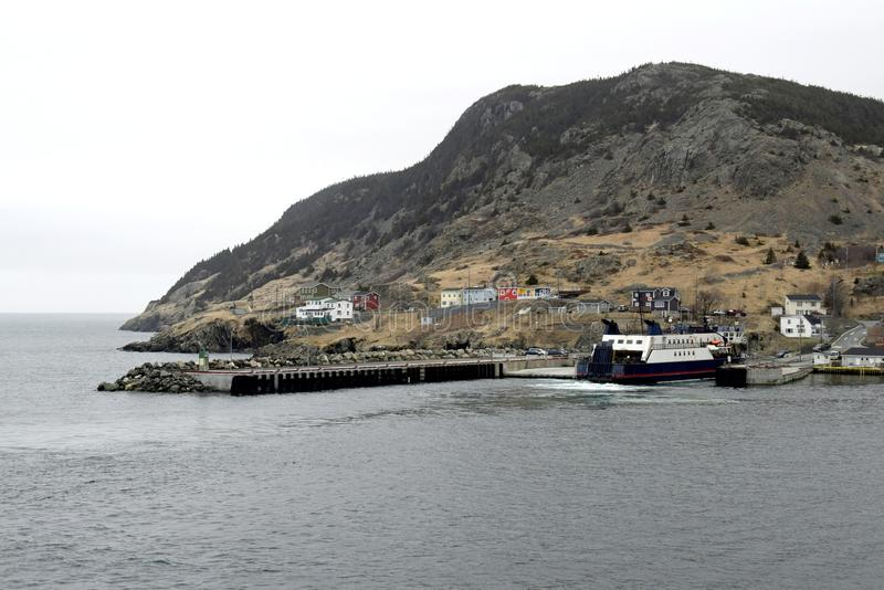 Ferry at Portugal Cove, NL. Ferry docking at the pier, a village and a mountain in the background, early Spring at Portugal Cove Newfoundland Canada royalty free stock photography