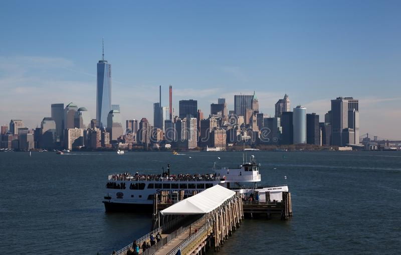 Ferry terminal at Statue of Liberty with NYC background. As visitors prepare to return to NYC after visiting the Statue of Liberty, NYC and lower Manhattan serve royalty free stock image