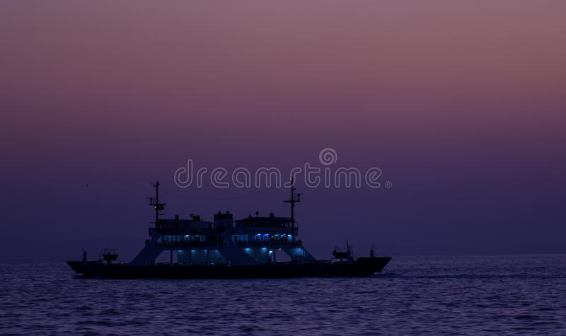 Ferry at Twilight. Ferryboat travelling in the middle of sea at twilight with tones of purple colour stock photo