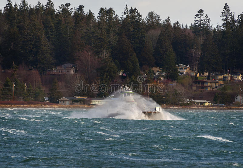 Ferryboat Sailing During a Winter Wind Storm. A Washington ferry boat is covered in ocean spray during a run from the mainland to an island in the Puget Sound stock images