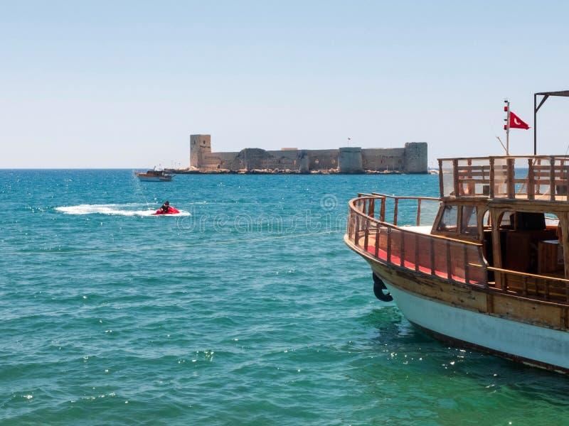 Ferryboat with turkish flag and man riding a hydrocycle against Maiden`s castle or Kizkalesi or Deniz kalesi royalty free stock photos