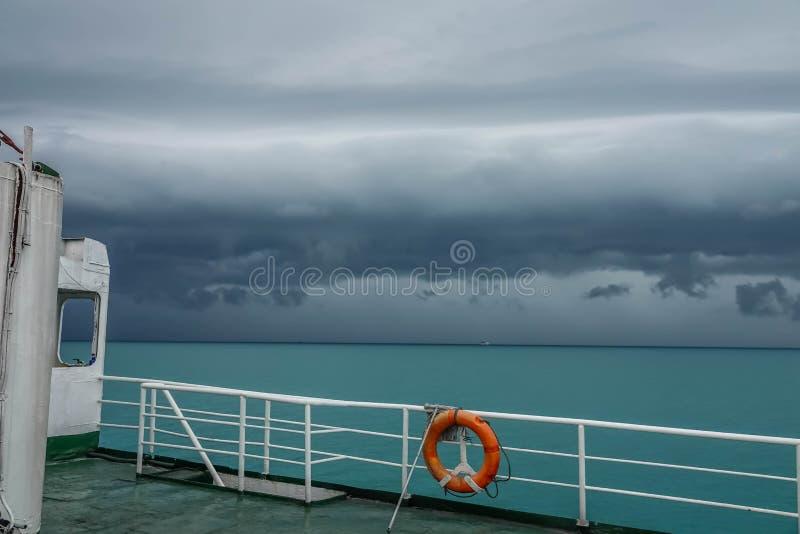 Ferryboat z pomarańczowym boja pierścionku żaglem w złej pogodzie z thunderclouds Morskiego bezpieczeństwa pojęcie zdjęcia royalty free