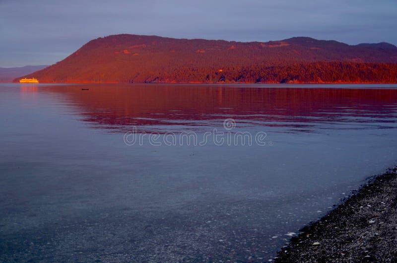 Ferryboat zaświecający czerwień świtu światłem zatok wyspy, gdy ono przechodzi puszek Satelitarny Chanel fotografia stock
