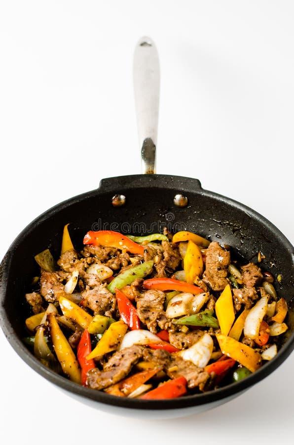 Fertanie Smażący wołowina stek z pieprzem na Odosobnionym tle zdjęcia stock