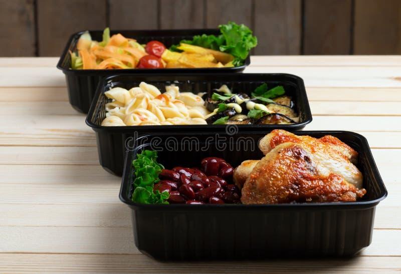 Fertiggerichte zu essen, Beh?lter mit gebratenes H?hnerfl?geln und rohem Gem?se auf rustikalem Hintergrund, Kirsch-Tomate und Mik stockbilder