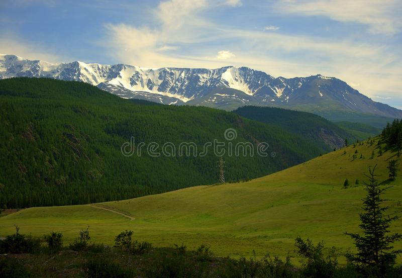 A fertile pasture in a valley near the slopes of a green hill and snow caps of mountain peaks in the background. North Kurai Range, Altai, Siberia, Russia stock photos