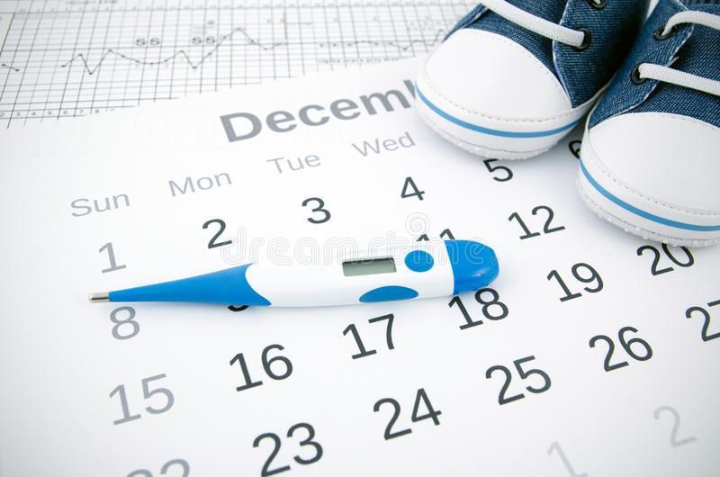 Fertility concept with thermometer on calendar. Electronic thermometer in fertility concept on calendar royalty free stock photography
