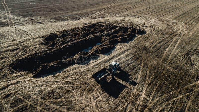 Fertilizzante sul campo Trattore vicino al mucchio di concime Rilevamento aereo fotografia stock libera da diritti