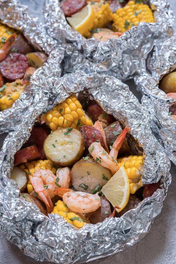 A fervura do camarão com folha da batata e do milho da salsicha embala foto de stock royalty free