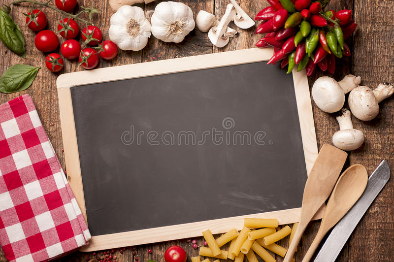 Fresh food. Italian food cooking. Tomatoes, basil, pasta and blackboard for your recipe on stone kitchen table. Top view with copy space stock photography