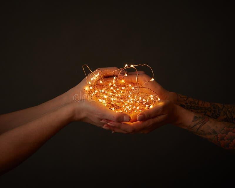 Festão amarela brilhante, mão fêmea das posses com tatuagem e mão do homem em torno de um fundo escuro com espaço para o texto foto de stock royalty free