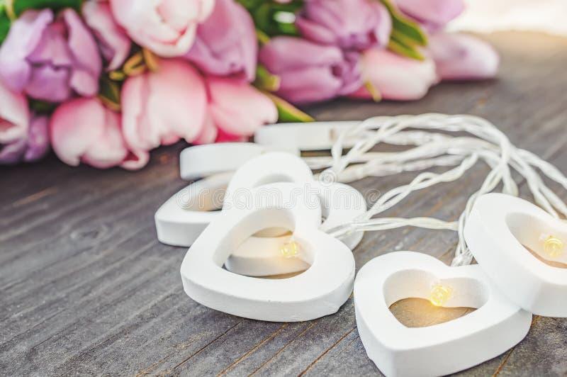 Festão bonita dos corações brancos em um fundo de tulipas cor-de-rosa congratulation Fundo festivo foto de stock