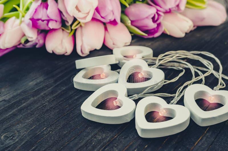 Festão bonita dos corações brancos em um fundo de tulipas cor-de-rosa congratulation Fundo festivo fotos de stock royalty free