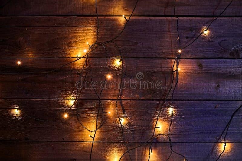 Festão de incandescência brilhante do Natal em um fundo de madeira fotografia de stock royalty free