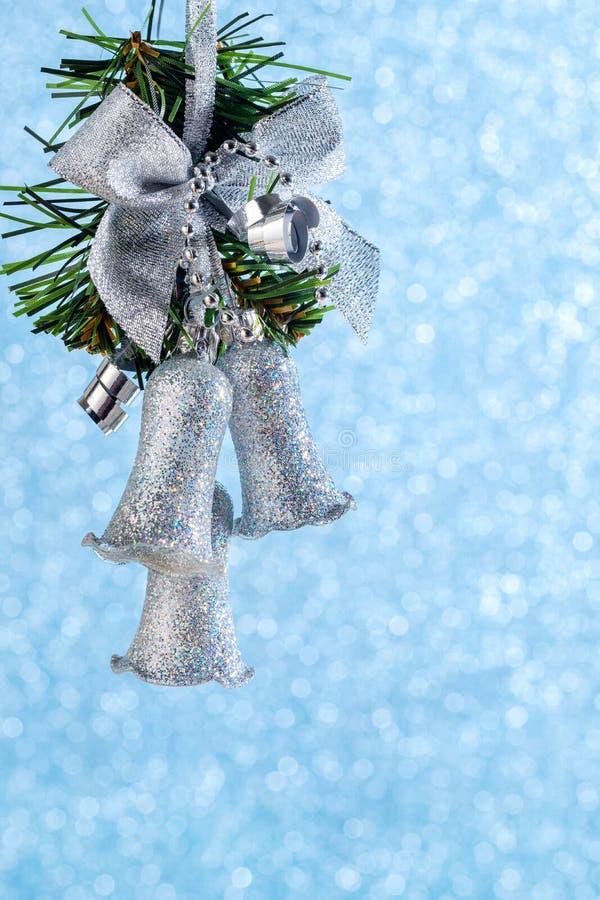 Festão de prata do Natal que pendura em uma fita em um fundo azul com bokeh imagens de stock royalty free