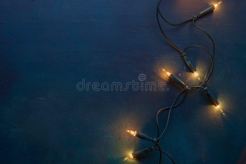 A festão do Natal ilumina-se no fundo de madeira escuro do vintage foto de stock