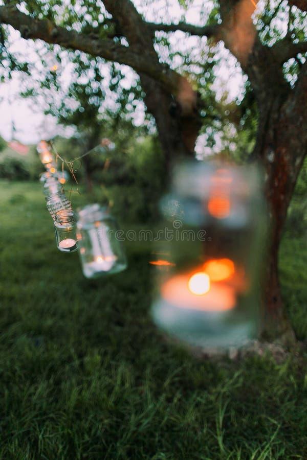 Festão dos frascos com a vela ardente que pendura em uma árvore no tempo da noite imagens de stock royalty free