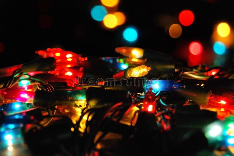 Festão elétrica de incandescência do Natal com luzes em um bokeh fotografia de stock