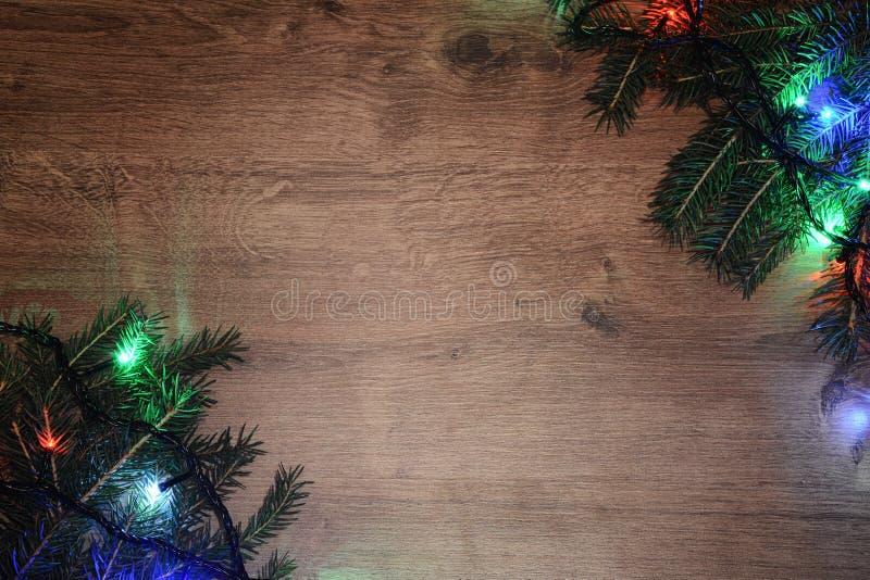 festão elétrica de Novo-ano em um fundo de madeira Bulbos brilhantes o fotografia de stock