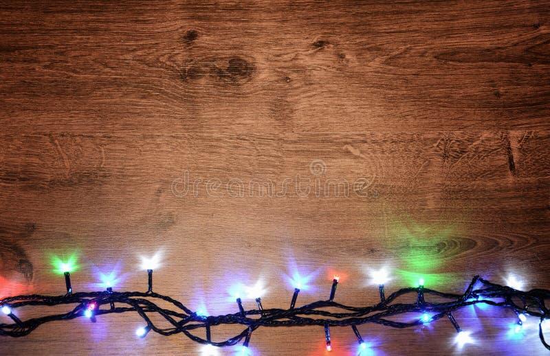 festão elétrica de Novo-ano em um fundo de madeira Bulbos brilhantes o fotos de stock