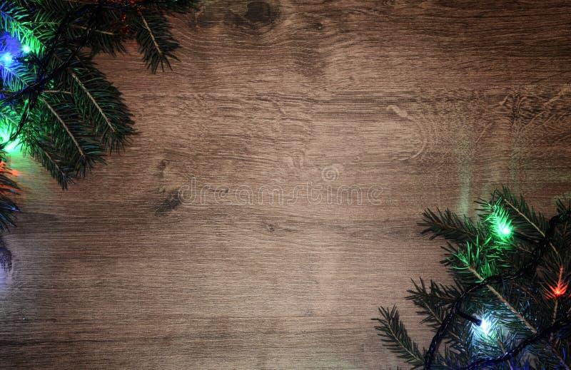 festão elétrica de Novo-ano em um fundo de madeira Bulbos brilhantes o imagens de stock