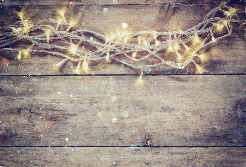 A festão morna do ouro do Natal ilumina-se no fundo rústico de madeira imagem filtrada com folha de prova do brilho