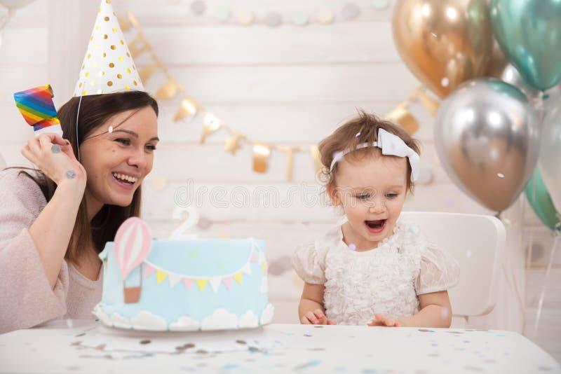 Festa de anos do bebê A mãe e sua filha comemoram e divertimento junto Partido da criança com decoração e bolo dos balões imagem de stock royalty free