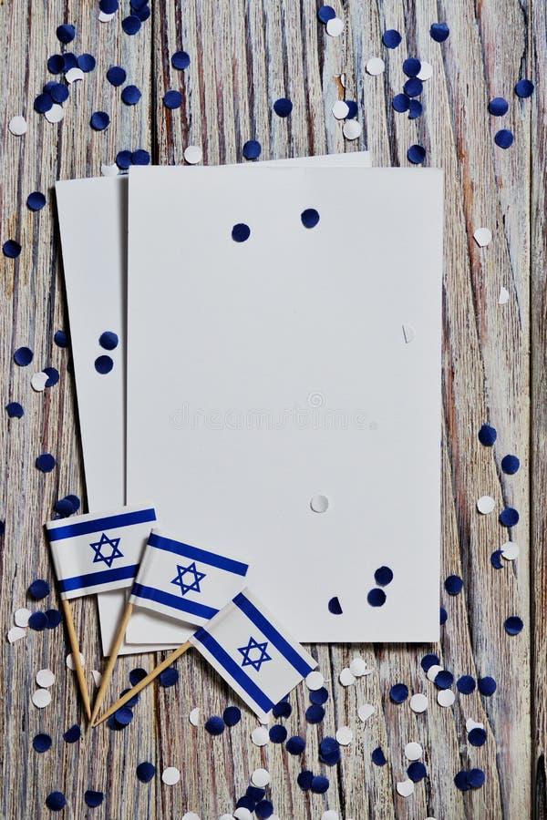 Festa dell'indipendenza di Israele 29 aprile 2020 coriandoli bianchi della carta blu con tre bandiere ed i fogli di carta bianchi fotografie stock libere da diritti