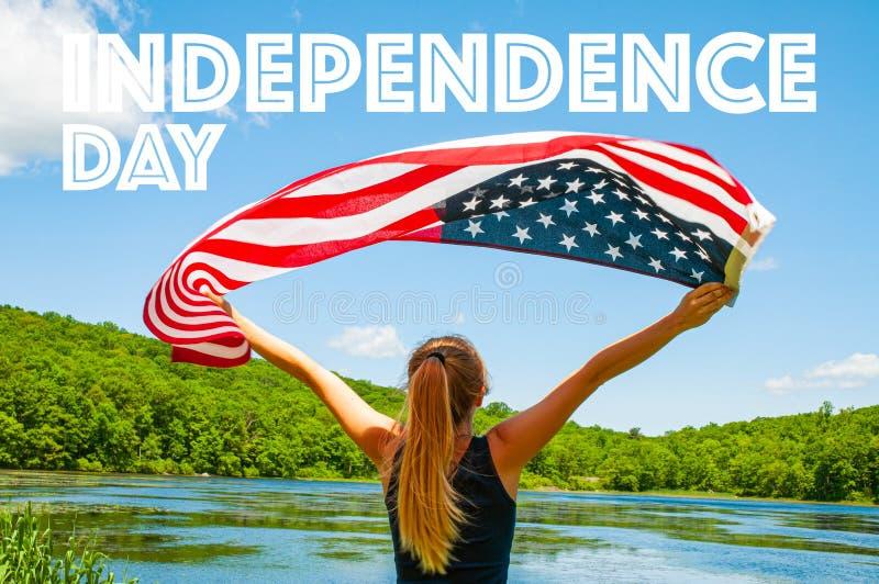 Festa dell'indipendenza felice, quarta di luglio Bandiera americana della tenuta della donna sul fondo del lago fotografie stock