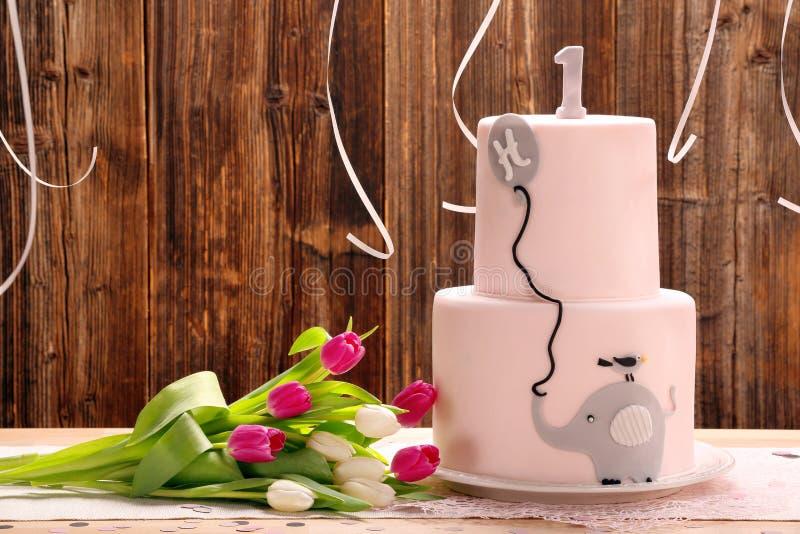 Festa di compleanno con la torta di compleanno rosa ed elefante su un di legno immagini stock
