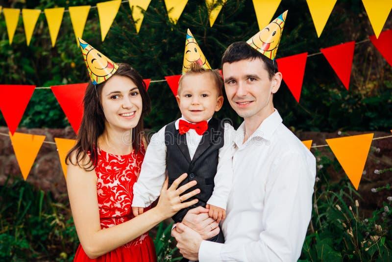 Festa di compleanno dei bambini di tema Un figlio della tenuta del padre e madre della famiglia di un anno sui precedenti di pian immagine stock