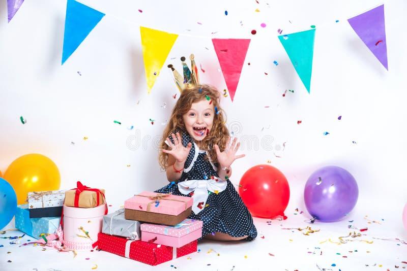 Festa di compleanno per il bambino sveglio Bambina che getta i coriandoli variopinti e che sembra felice sulla festa di compleann immagini stock libere da diritti