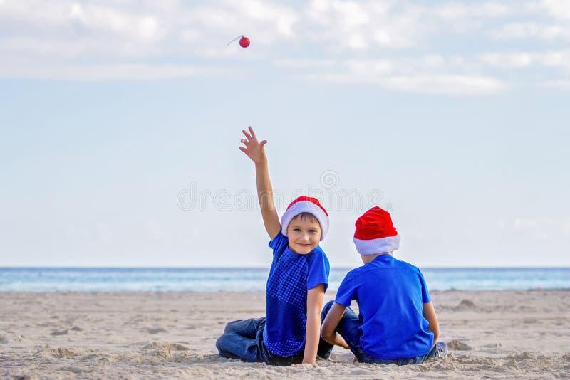 Festa di Natale Bambini in cappelli rossi di Santa alla spiaggia soleggiata fotografia stock libera da diritti